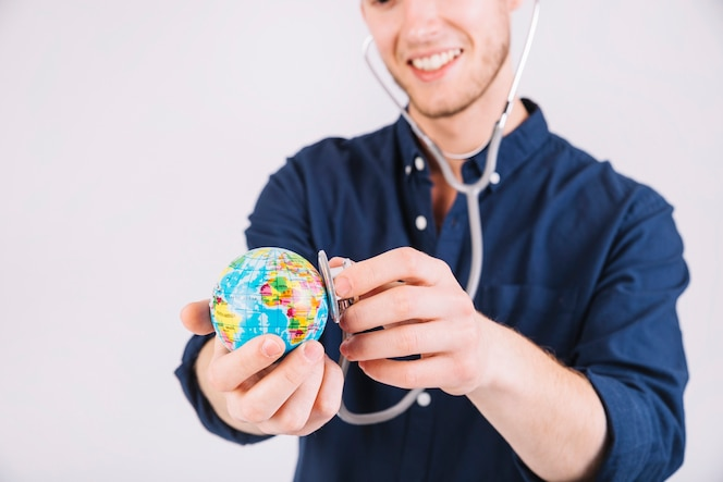 Sonriente joven examinando globo con estetoscopio