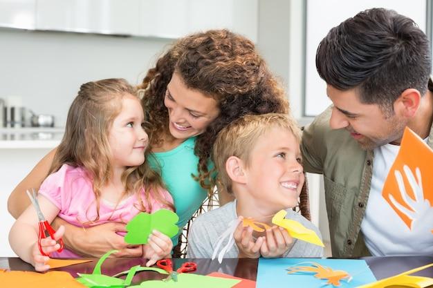 Sonriente joven familia haciendo manualidades en la mesa