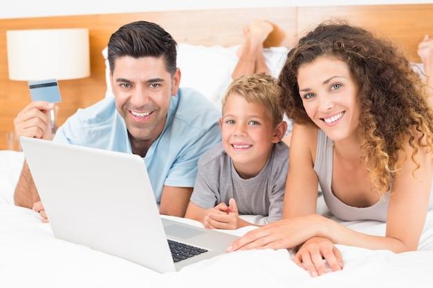 Sonriente joven familia utilizando la computadora portátil para comprar en línea juntos en la cama