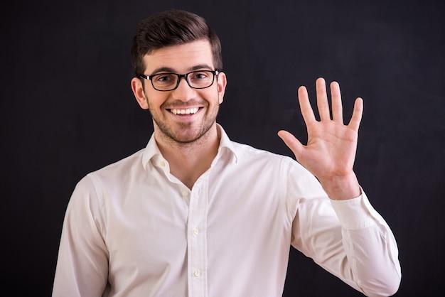 Sonriente, joven con gafas está levantando su mano.