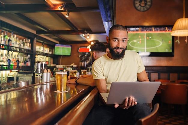 Sonriente joven guapo bebiendo cerveza en el bar y usando la computadora portátil