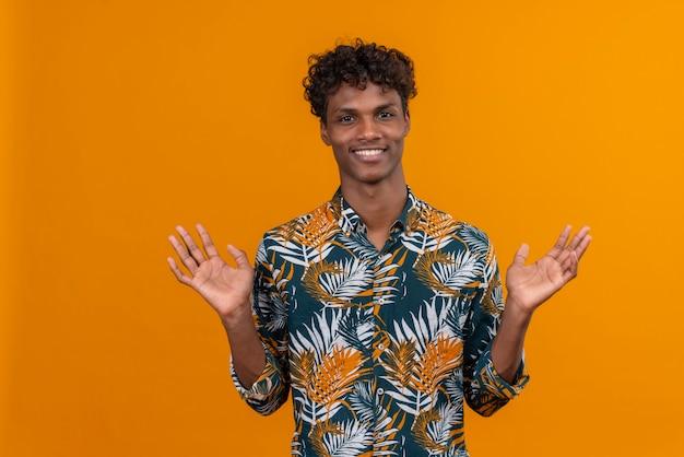 Sonriente joven guapo en camisa abriendo los brazos abiertos mirando hacia arriba sobre un fondo naranja