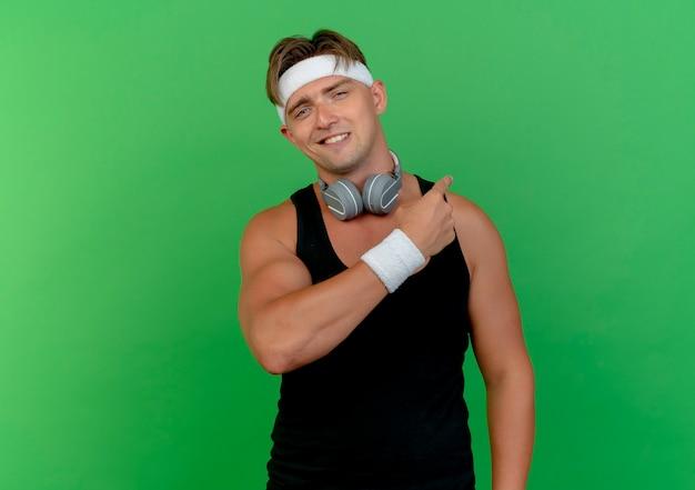 Sonriente joven guapo deportivo con diadema y muñequeras con auriculares en el cuello apuntando detrás aislado en la pared verde