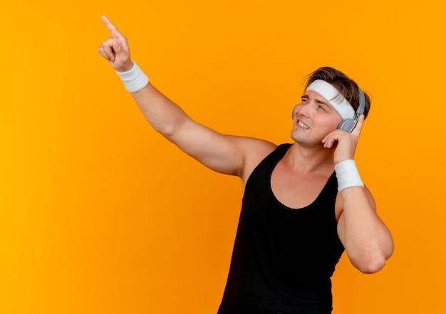 Sonriente joven guapo deportivo con diadema y muñequeras con auriculares mirando y apuntando hacia arriba y poniendo el dedo en los auriculares aislados en la pared naranja