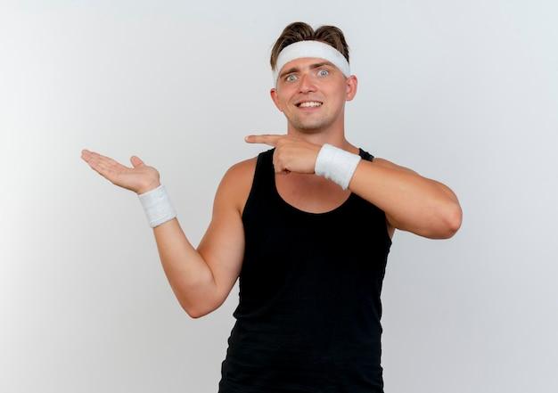 Sonriente joven guapo deportivo con diadema y muñequeras mostrando la mano vacía y apuntando a ella aislada en la pared blanca