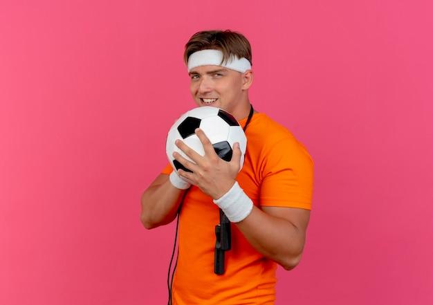 Sonriente joven guapo deportivo con diadema y muñequeras con saltar la cuerda alrededor del cuello sosteniendo un balón de fútbol aislado en la pared rosa
