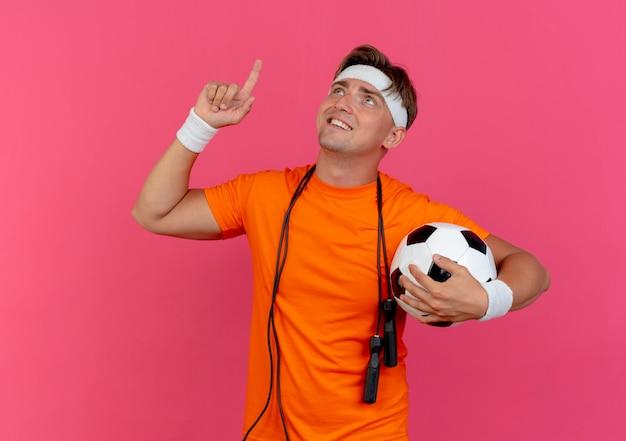 Sonriente joven guapo deportivo con diadema y muñequeras con saltar la cuerda alrededor del cuello sosteniendo un balón de fútbol mirando y apuntando hacia arriba aislado en la pared rosa