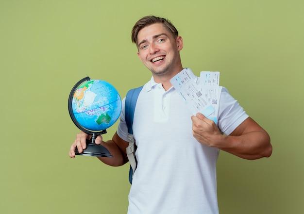 Sonriente joven guapo estudiante vistiendo bolsa trasera sosteniendo boletos y globo aislado en verde oliva