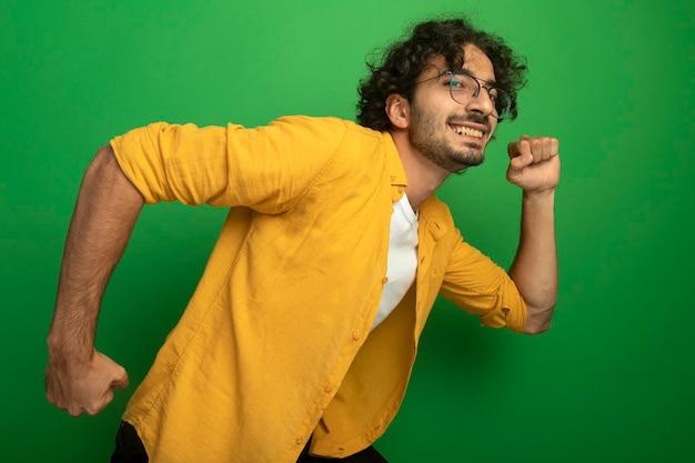 Sonriente joven guapo con gafas mirando al frente apretando los puños corriendo aislado en la pared verde