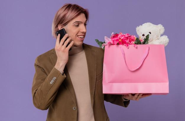 Sonriente joven guapo hablando por teléfono y mirando la bolsa de regalo rosa con flores y osito de peluche