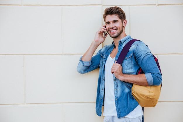 Sonriente joven guapo con mochila de pie y hablando por teléfono móvil
