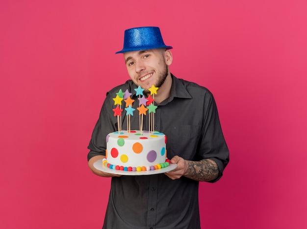 Sonriente joven guapo partido eslavo con sombrero de fiesta sosteniendo pastel de cumpleaños con estrellas mirando a cámara aislada sobre fondo carmesí con espacio de copia