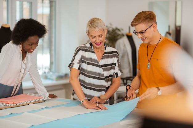 Sonriente joven guapo sastre cortando la tela mientras está de pie junto a sus colegas en un estudio.