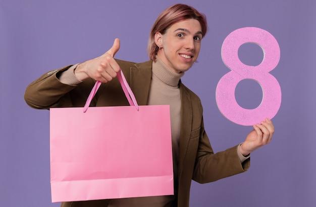Sonriente joven guapo sosteniendo una bolsa de regalo rosa y el número ocho apuntando hacia arriba