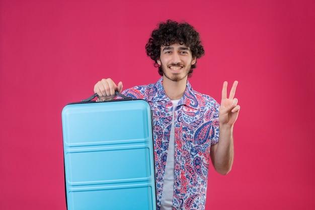 Sonriente joven guapo viajero rizado hombre sujetando la maleta y haciendo el signo de la paz en la pared rosa aislada con espacio de copia