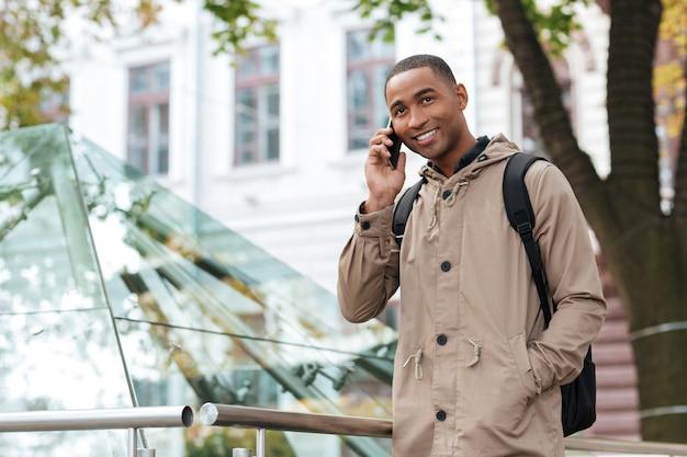 Sonriente joven hablando por su teléfono en la calle