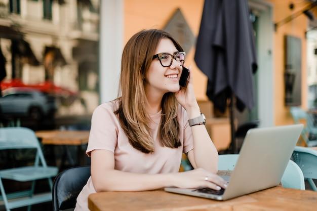 Sonriente joven hablando por teléfono y escribiendo en la computadora portátil en el café al aire libre