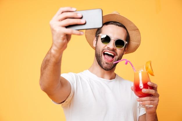 Sonriente joven hacer selfie por teléfono con cóctel.