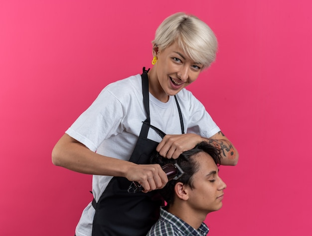 Sonriente joven hermosa barbero en uniforme sosteniendo herramientas de peluquero y haciendo corte de pelo para niño aislado sobre fondo rosa