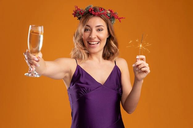 Sonriente joven hermosa chica con vestido púrpura con corona sosteniendo bengalas y sosteniendo una copa de champán en la cámara aislada sobre fondo marrón