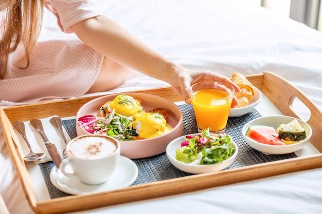 Sonriente joven hermosa mujer desayunando en la cama en la acogedora habitación de hotel
