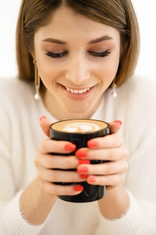 Sonriente joven hermosa mujer feliz con cabello largo disfrutando de capuchino sobre fondo blanco. mujer de belleza disfrutando de café. taza de bebida caliente.