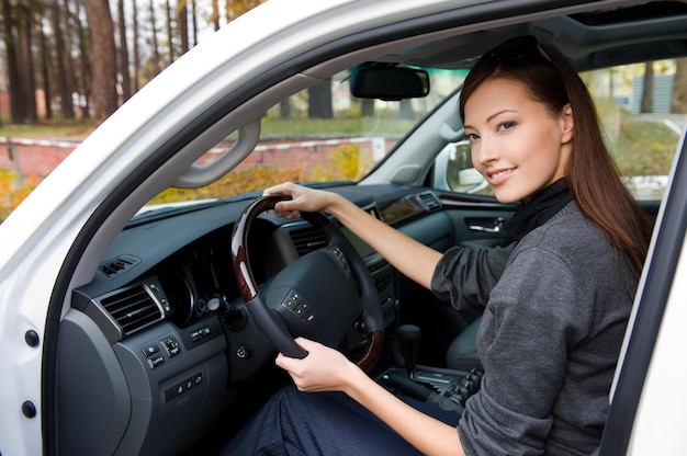 Sonriente joven hermosa mujer sentada en el coche nuevo - al aire libre