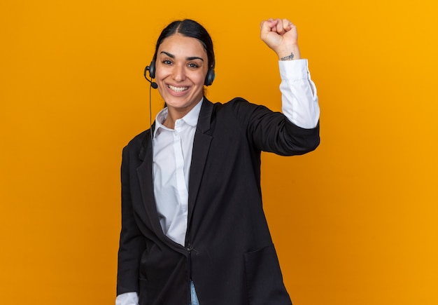 Sonriente joven hermosa mujer vestida con blazer negro con auriculares mostrando gesto de sí
