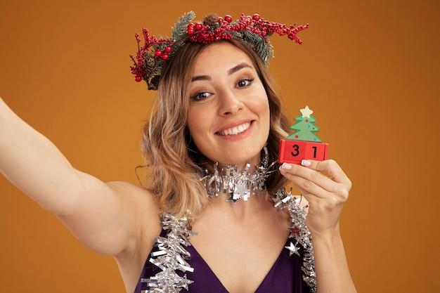 Sonriente joven hermosa niña con vestido púrpura y corona con guirnalda en el cuello sosteniendo juguetes de navidad y cámara aislada sobre fondo marrón