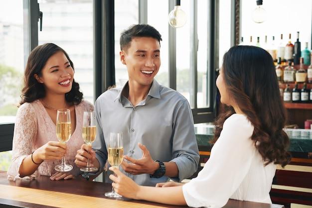 Sonriente joven hombre asiático y dos mujeres animando con champán en el bar