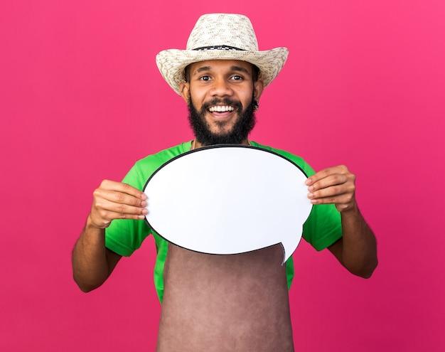 Sonriente joven jardinero afroamericano con sombrero de jardinería sosteniendo el bocadillo de diálogo