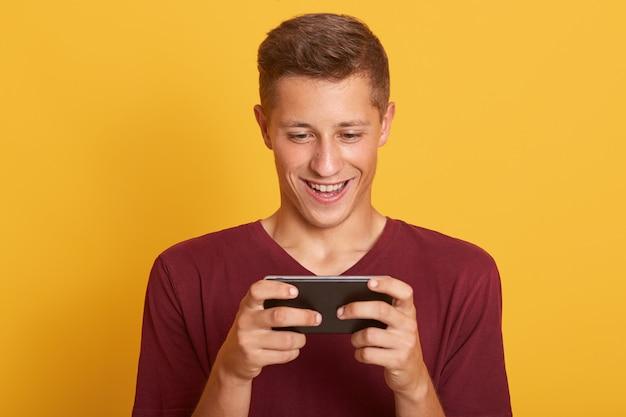 Sonriente joven jugando en el teléfono inteligente, se ve feliz y concentrado, mirando sonriente a la pantalla de su dispositivo