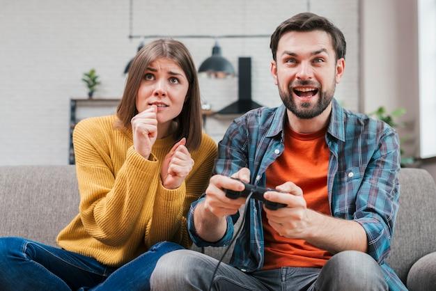 Sonriente joven jugando el videojuego con su esposa