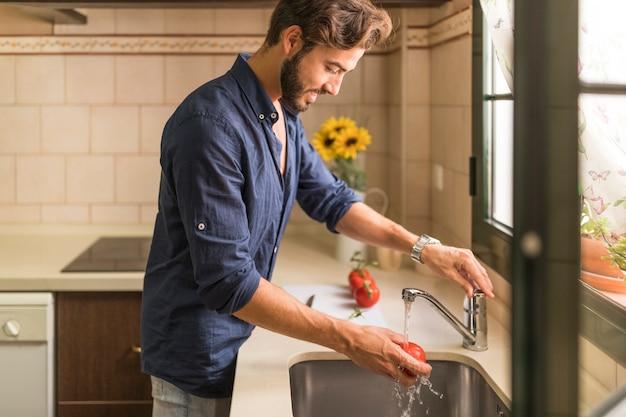 Sonriente joven lavando el tomate en el fregadero