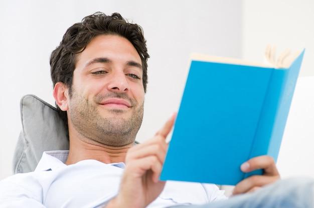 Sonriente joven leyendo un libro de novelas mientras se relaja en el sofá