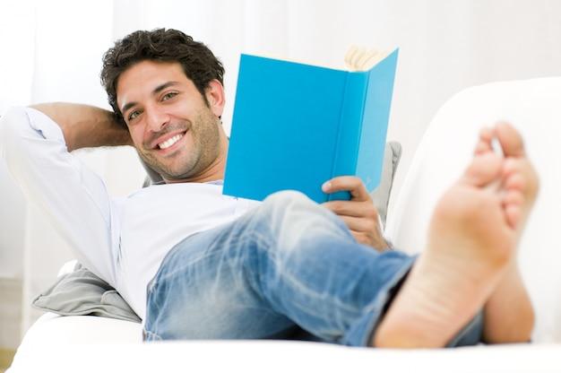Sonriente joven leyendo un libro y relajándose en el sofá en casa