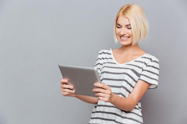 Sonriente joven linda con cabello rubio con tableta sobre pared gris