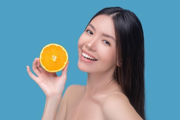 Sonriente joven linda sosteniendo una rodaja de naranja y sintiéndose bien