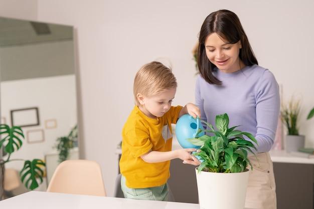 Sonriente joven madre ayudando a su hijo a regar la planta doméstica con regadera en casa