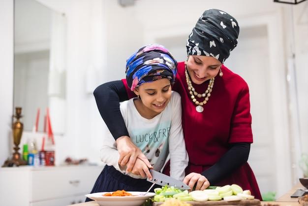Sonriente joven madre y niña bonita en delantales cortan ensalada fresca sobre tabla de madera con un cuchillo afilado en la mesa en la gran cocina cómoda en casa