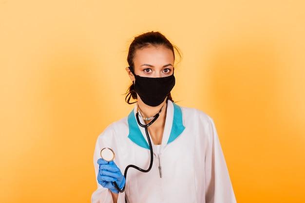 Sonriente joven médico afroamericano en máscara médica sosteniendo una jeringa