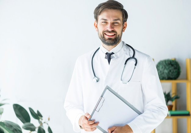 Sonriente joven médico con portapapeles