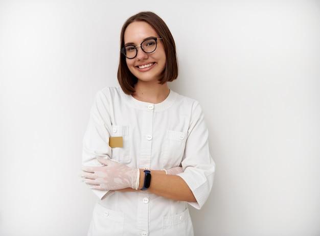 Sonriente joven médico interno posando con los brazos cruzados sobre fondo blanco con espacio para texto