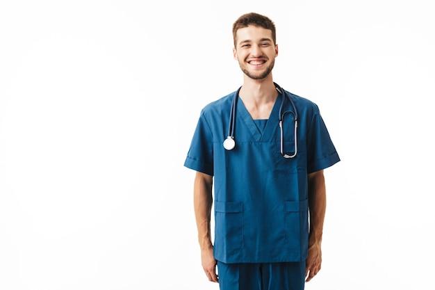 Sonriente joven médico en uniforme con fonendoscopio en el cuello con alegría