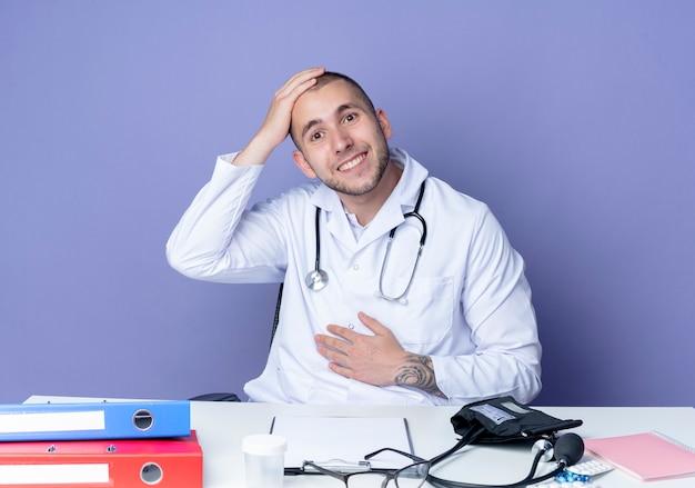 Sonriente joven médico vistiendo bata médica y estetoscopio sentado en el escritorio con herramientas de trabajo poniendo las manos en el vientre y la cabeza aislada en la pared púrpura