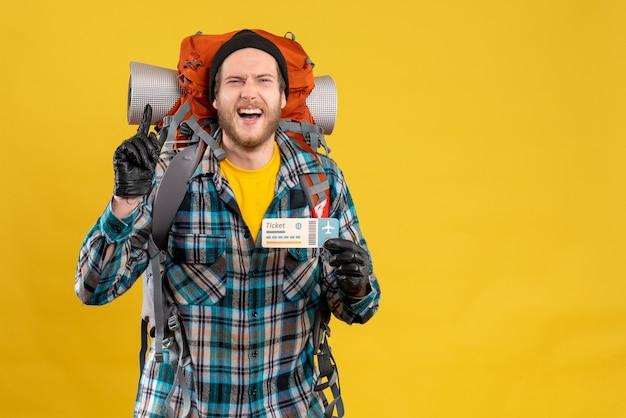 Sonriente joven mochilero con sombrero negro sosteniendo billete de avión