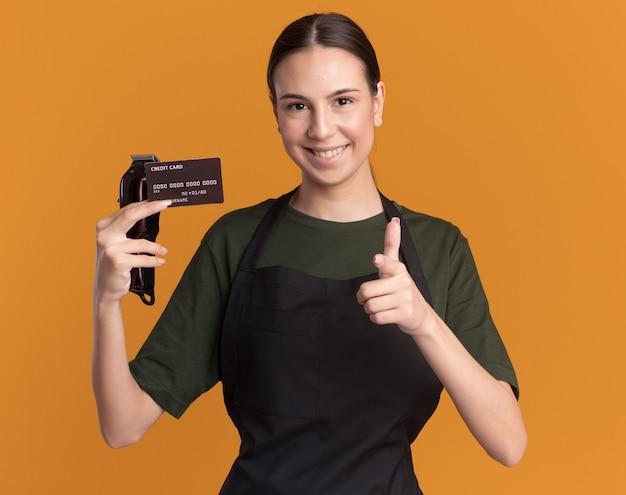 Sonriente joven morena barbero en uniforme sostiene cortapelos y tarjeta de crédito apuntando a la cámara