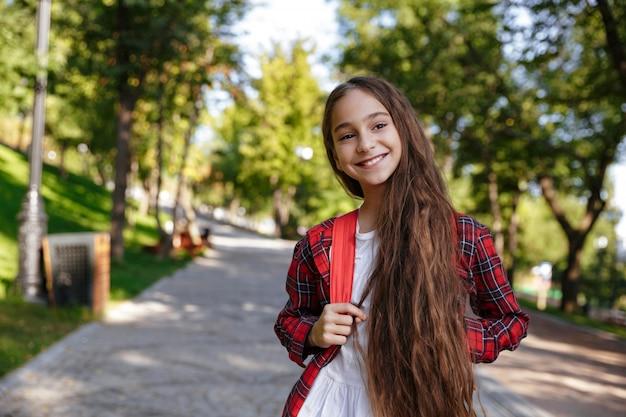 Sonriente joven morena posando en el parque