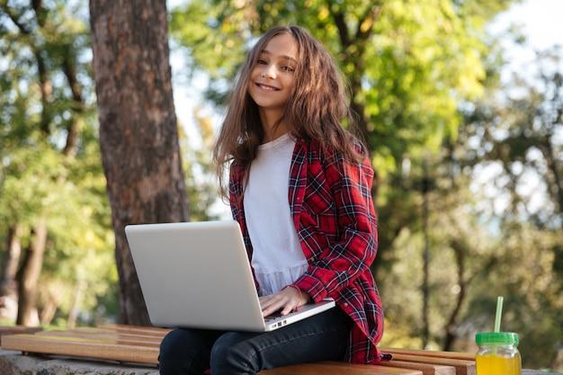 Sonriente joven morena sentada en el parque con ordenador portátil
