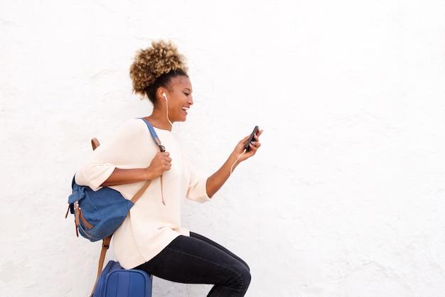Sonriente joven mujer africana sentada en maleta y mirando el teléfono